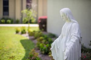 A white statue of Mary Mother of God in the garden of Little Flower Catholic Church