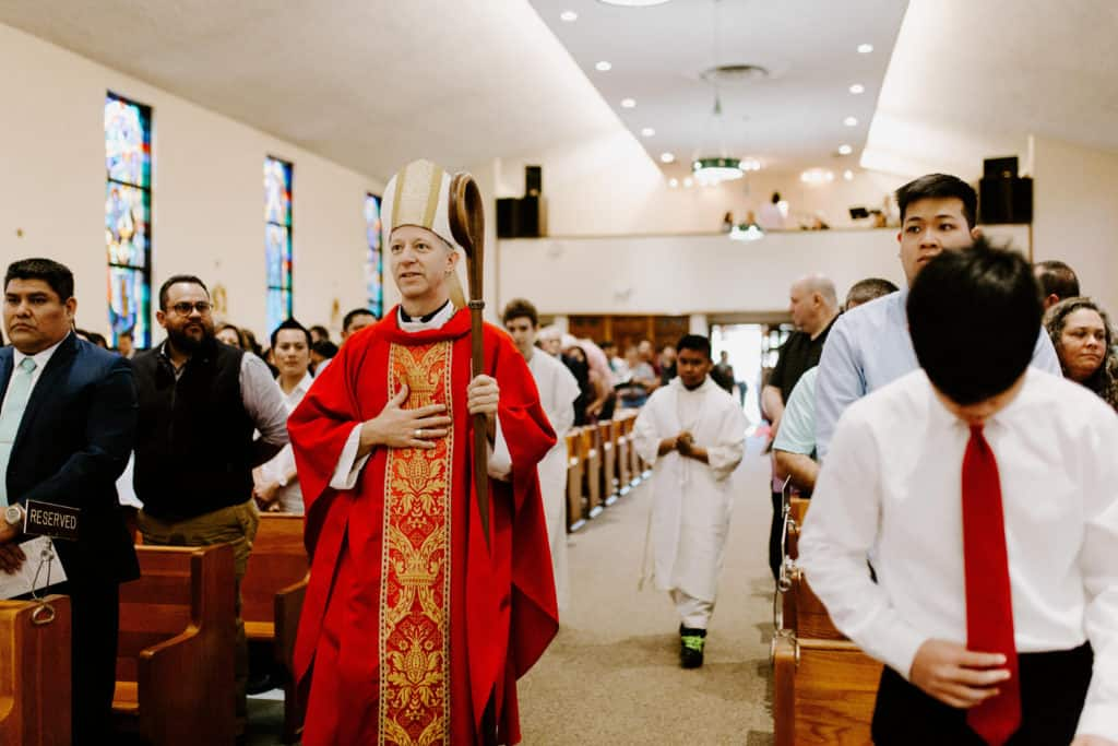 Bishop Bill Wack wearing red vestments processes into Mass at the 2019 Confirmation Mass at Little Flower Catholic Church