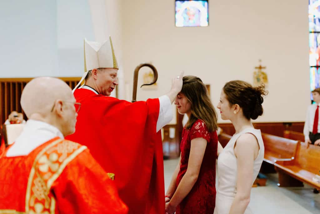 Bishop Bill Wack confirms a female student at the 2019 Little Flower Catholic Church graduation Mass
