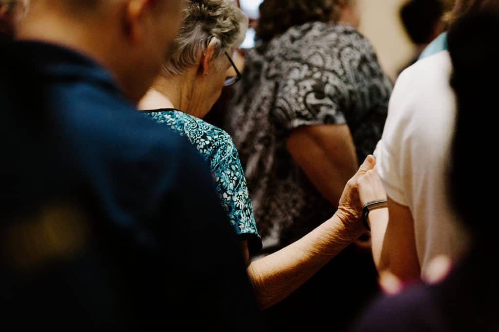 A closeup of a woman in a blue shirt holding hands during the Our Father at 2019 Confirmation Mass at Little Flower Catholic Church