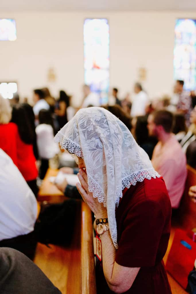 A parishioner wearing a veil bows her head in prayer during the 2019 Confirmation Mass at Little Flower Catholic Church