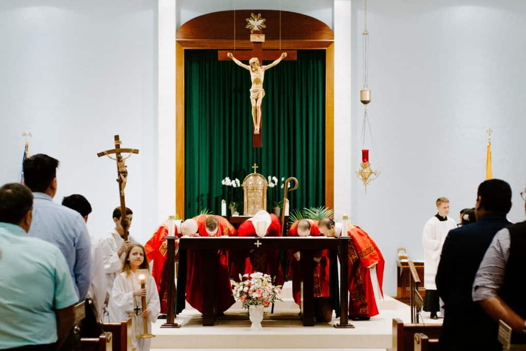 Bishop Bill Wack and Fr. Matt Worthen kiss the altar after the 2019 Confirmation Mass at Little Flower Catholic Church