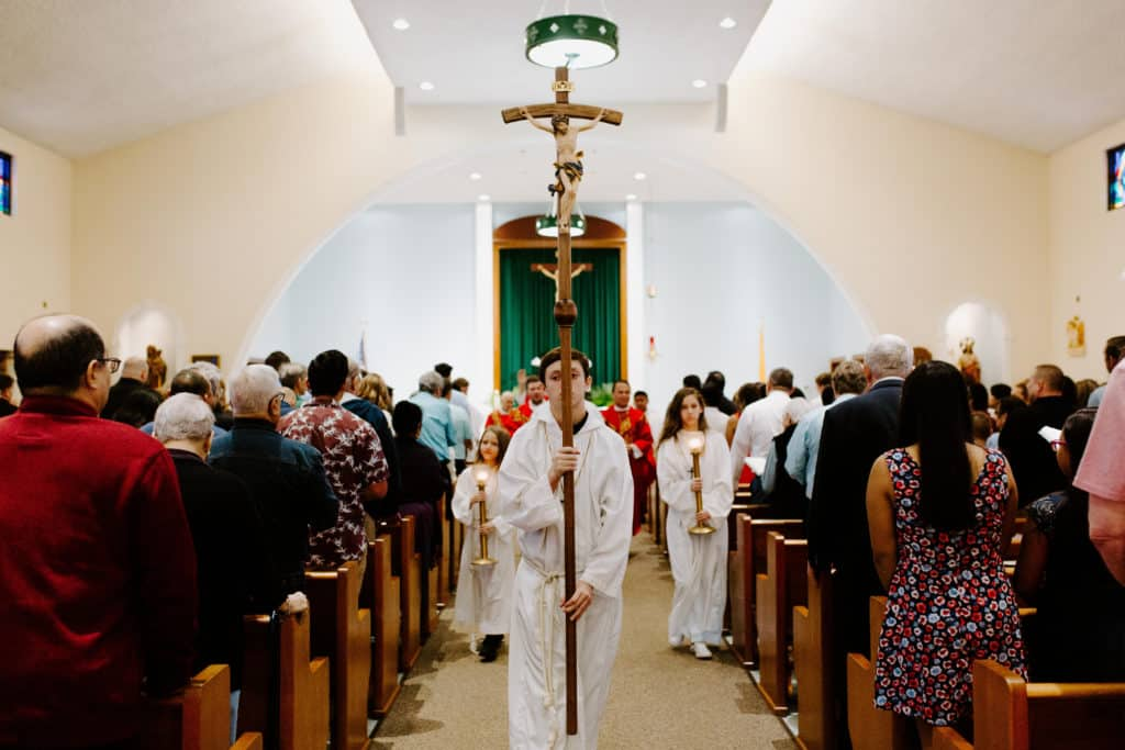 An altar server carrying the cross leads the procession after the 2019 Confirmation Mass at Little Flower Catholic Church