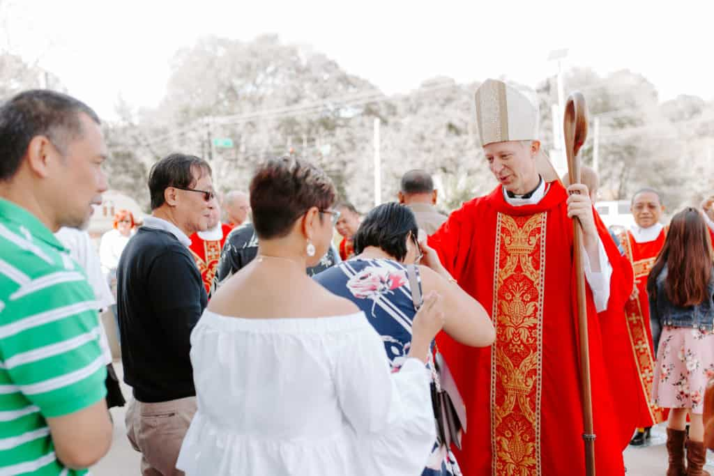 Bishop Bill Wack gives a blessing to a Filipino parishioner at the 2019 Confirmation Mass at Little Flower Catholic Church