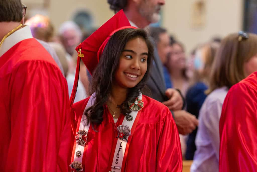 A female student wearing her cap and gown during the graduation Mass of the 2019 Little Flower Catholic School 8th graders