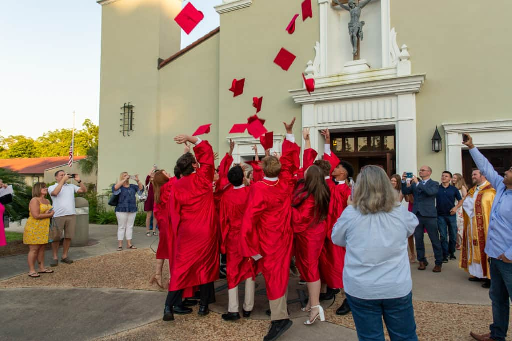 Graduating 8th graders of Little Flower Catholic School throw their hats in the air after their award ceremony