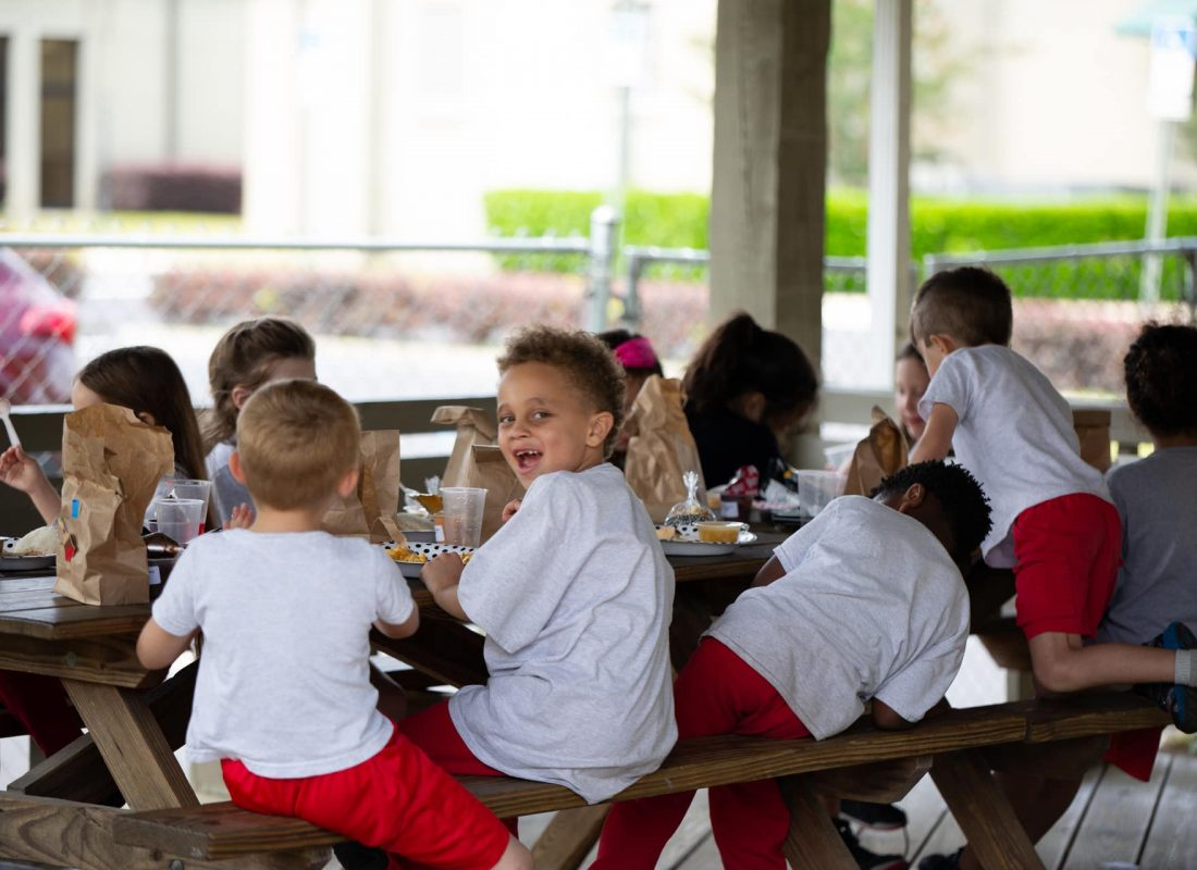 A group of young kindergarten students laughing and smiling in the pavilion at Little Flower Catholic School