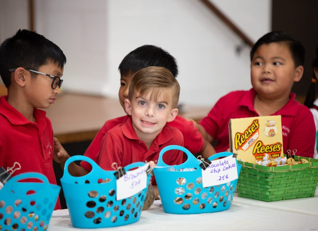 A smiling student in front of a blue basket at Little Flower Catholic School