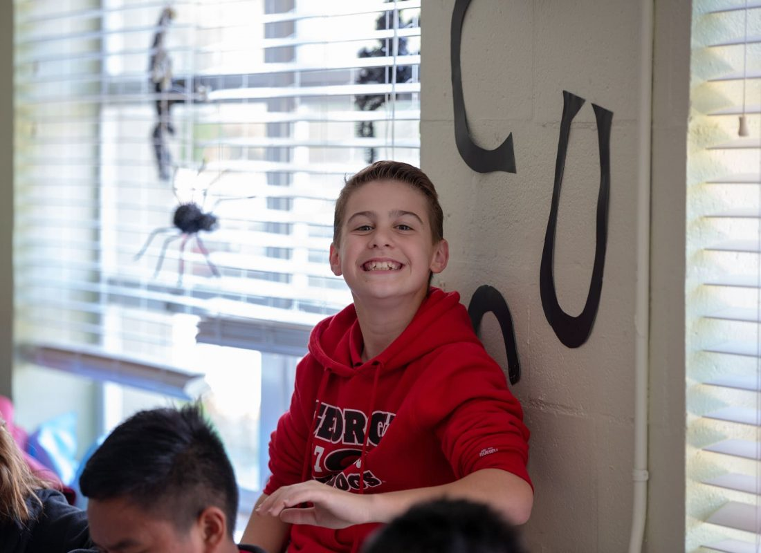 A student smiling in front of the windows of his classroom at Little Flower Catholic School