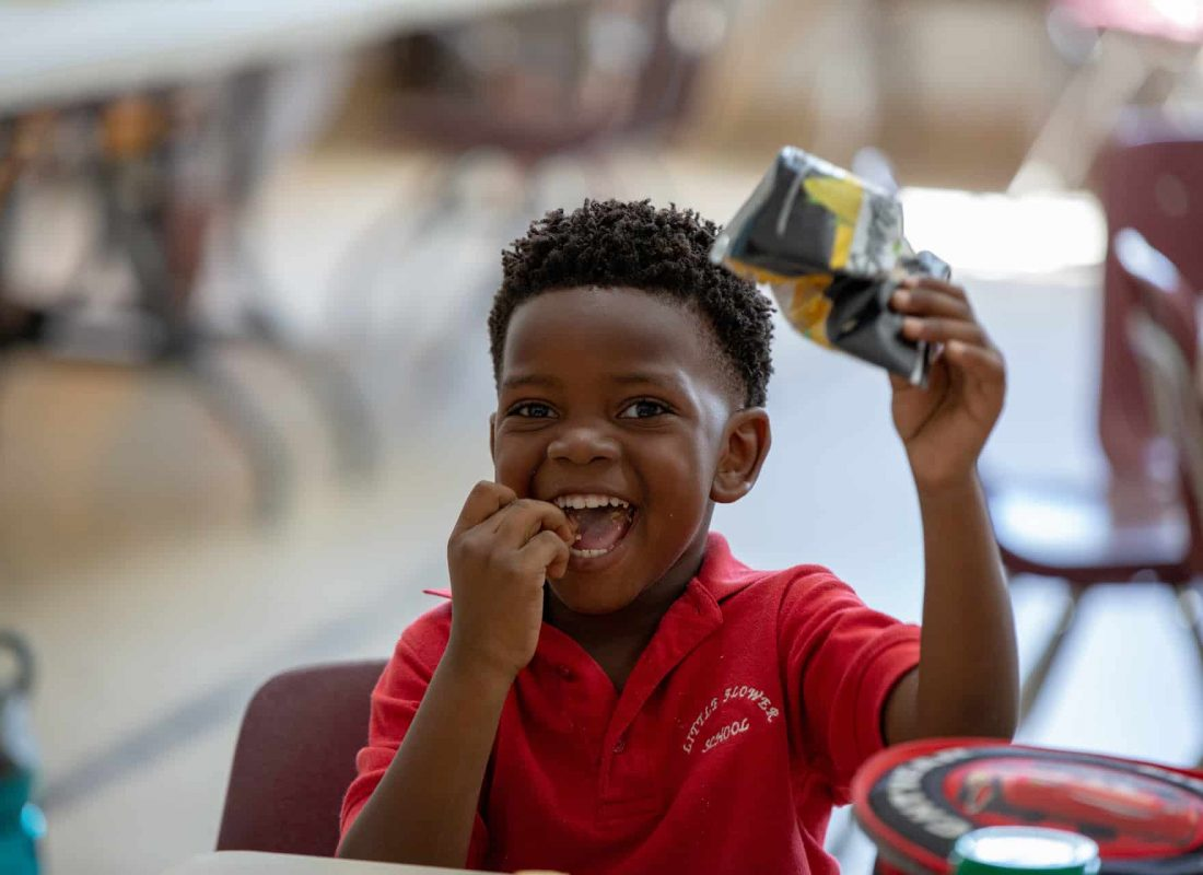 A student eating his bag of chips during lunch atLittle Flower Catholic School