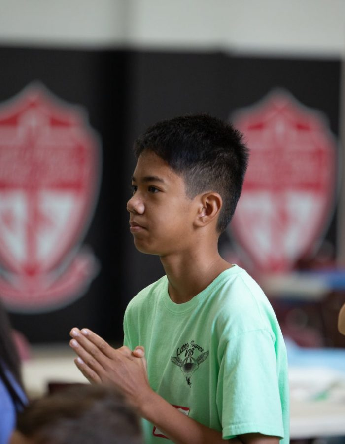A student in a green shirt with folded praying hands at Vacation Bible School at Little Flower Catholic Church