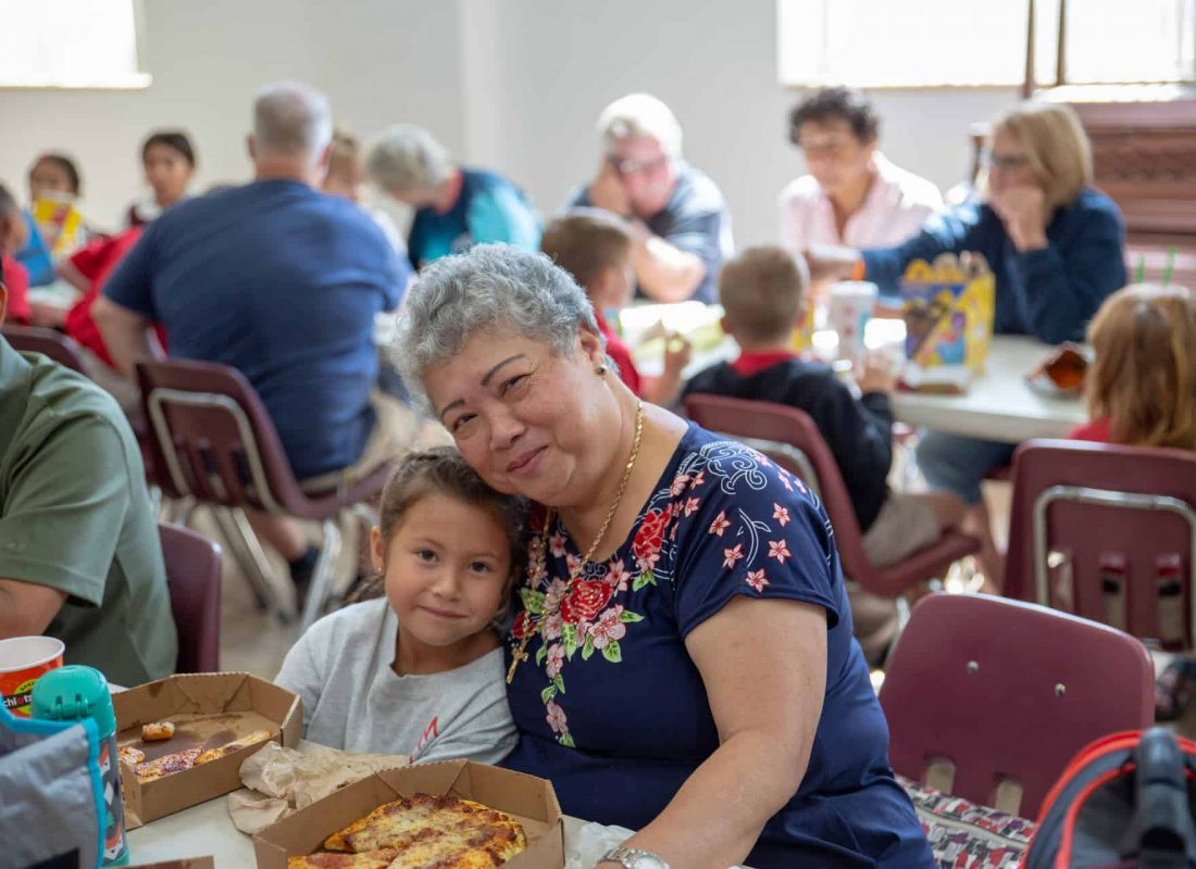 A grandmother poses smiling alongside her granddaughter at Little Flower Catholic School during lunch