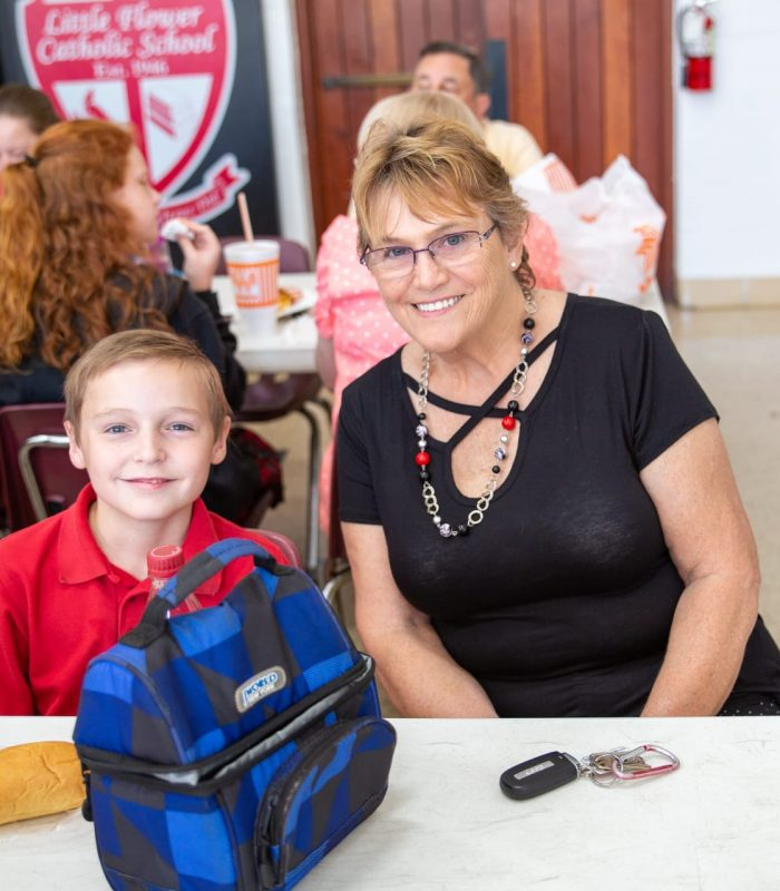 A grandmother poses smiling alongside her grandson and lunchbox at Little Flower Catholic School during lunch