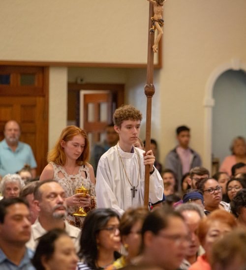 An Altar Server processes with the crucifix into Mass at Little Flower Catholic Church