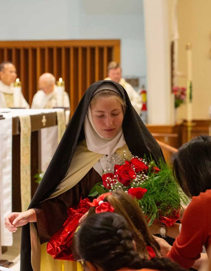 A student dressed as St. Therese of Lisieux holding flowers at Mass at Little Flower Catholic Church