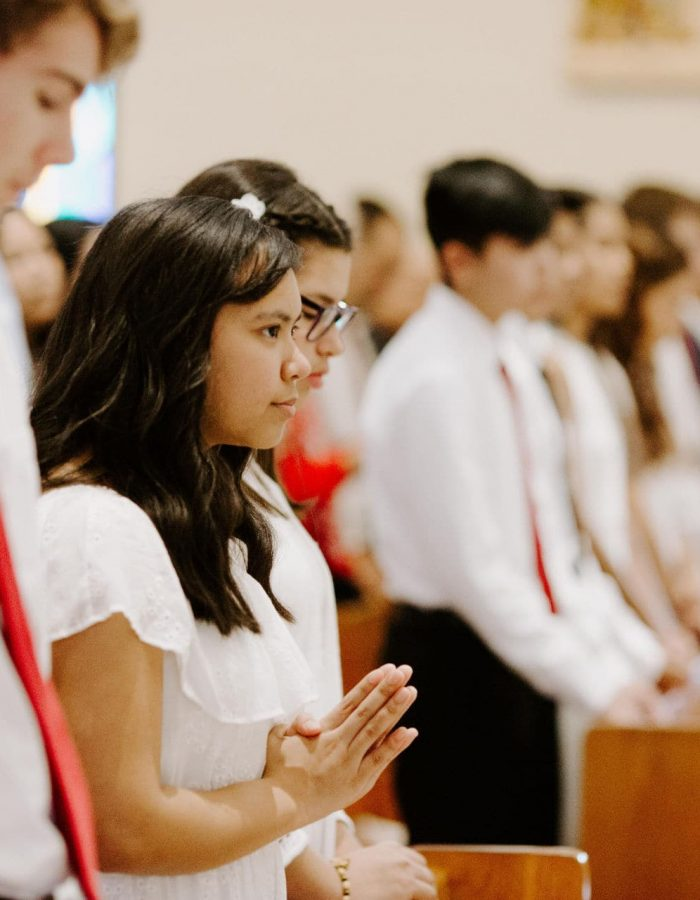 Students with their hands folded pray and prepare for the 2019 Confirmation Mass at Little Flower Catholic Church