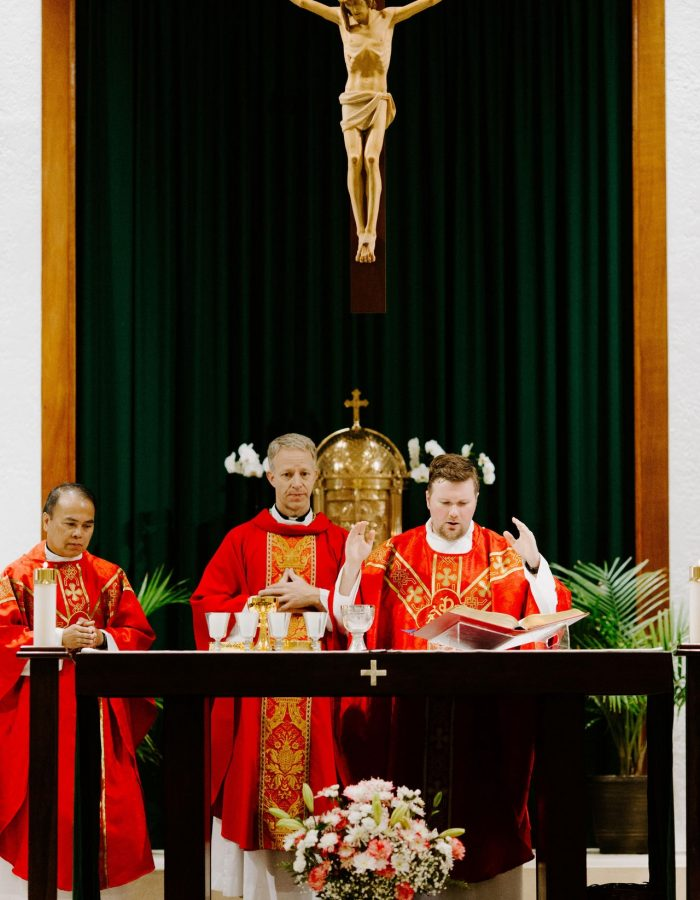 Bishop Bill Wack and Fr. Matt Worthen under the crucifix read from the Missal during the consecration at the 2019 Confirmation Mass at Little Flower Catholic Church
