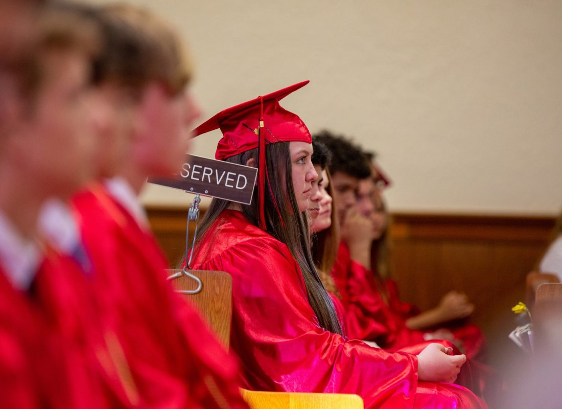 A female student sits in a pew, listening to the homily at her 8th grade graduation ceremony at Little Flower Catholic School