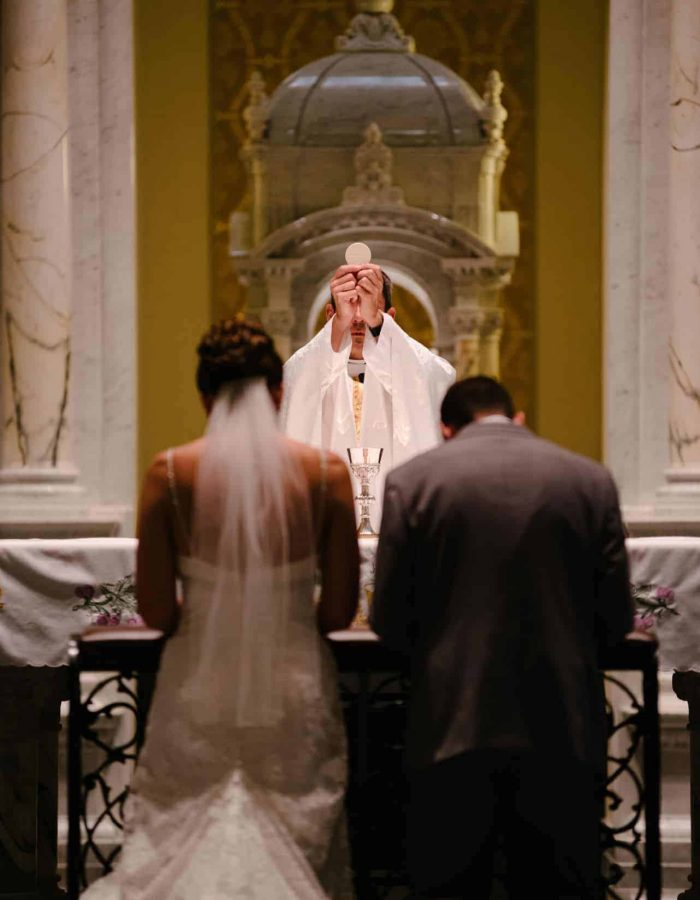 A couple kneels during the consecration of Mass at their wedding