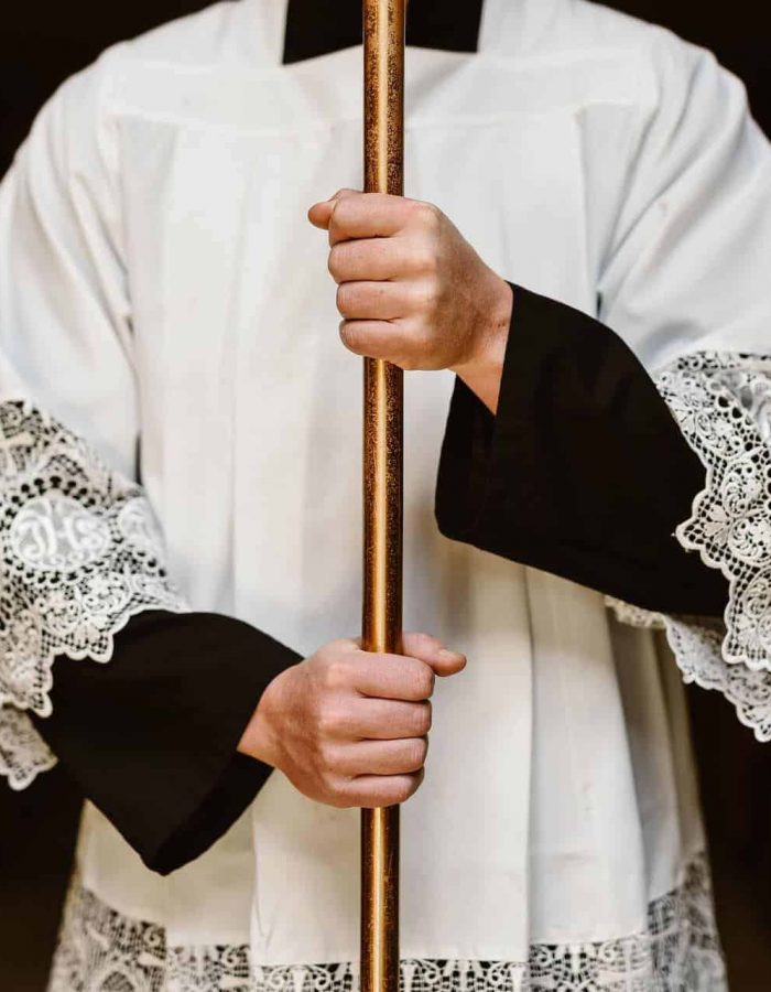 A seminarian holding a cross while dressed in a cassock and surplice
