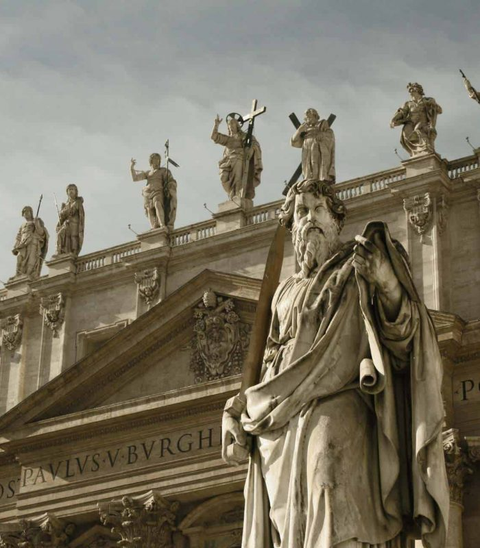 A statue of St. Peter in the foreground, with the saints behind him at the Vatican